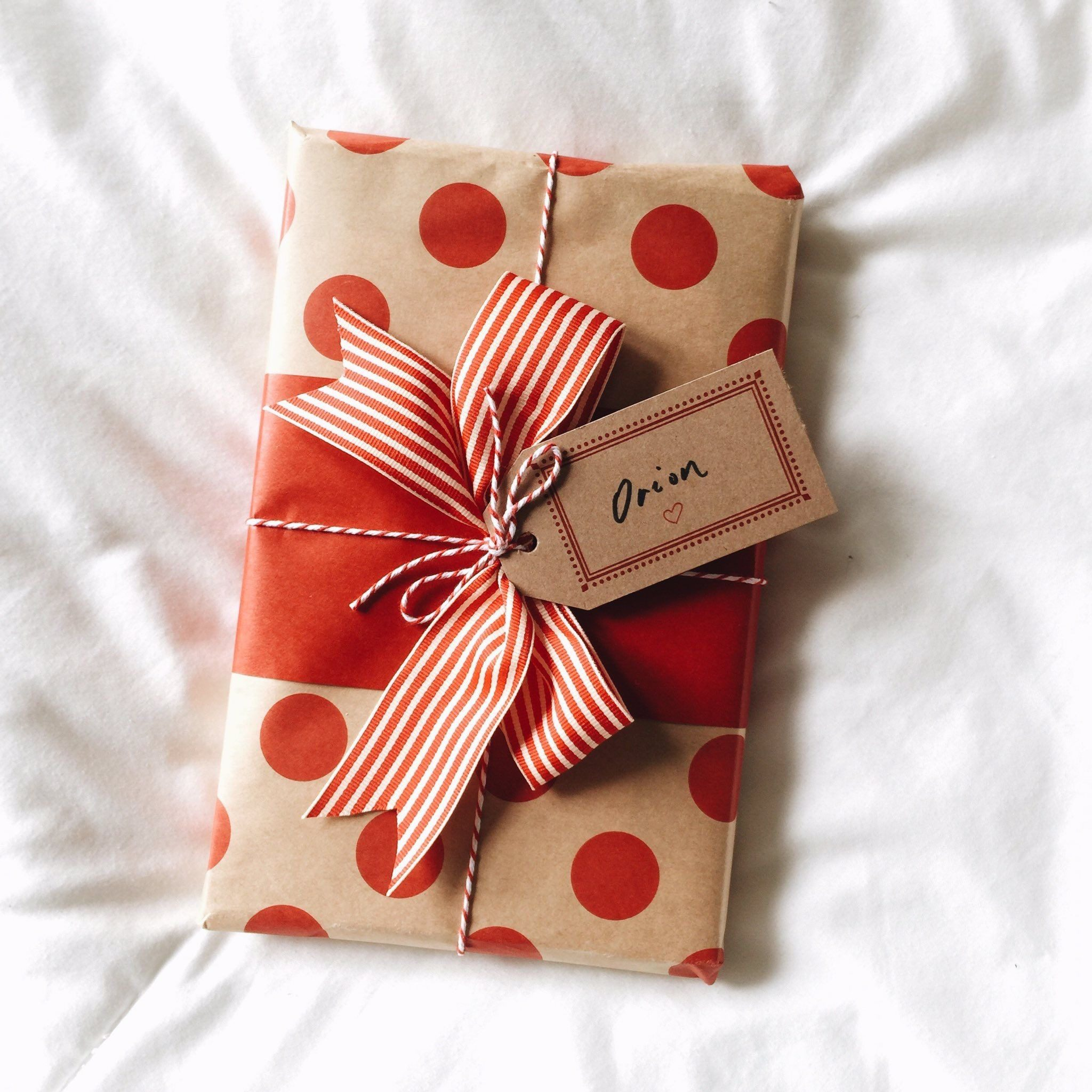 Red polka dot Christmas gift with ribbon on white background